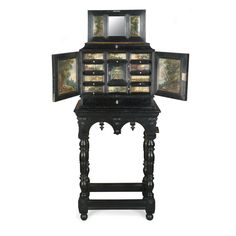 Antwerp School Cabinet: An ebony cabinet on a stand with a rectangular lifting top fitted with a panelled mirror flanked by two landscapes, above 2 panelled doors.  c.17th Century
