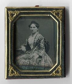 Dreiviertelporträt einer unbekannten jungen Frau. Sie trägt ein kariertes Kleid und sitzt auf einem Stuhl (Rokokoformen). Ihren rechten Arm stützt sie auf einem Tisch ab. In der linken Hand hält sie ein halbgeöffnetes Buch. Typische Accessoires sind auch hier Schmuckstücke: Ohrringe, Brosche, Armband und Ring.