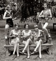 Girls playing uke on a park bench in their swimsuits. Taken on July 9, 1926 in Washington, DC.