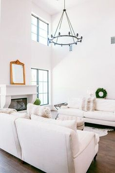 New Build Modern Farmhouse Home Tour with Holly Christian Hayes - Living Room - Minimalist Design - Minimal Home Design - Home Decor - Interior Design - White Sofas - Cow Hide Sofa - European Farmhouse - Black Framed Windows with White Walls - Gold Mirror on Mantle - Wagon Wheel Chandelier - Round Chandelier
