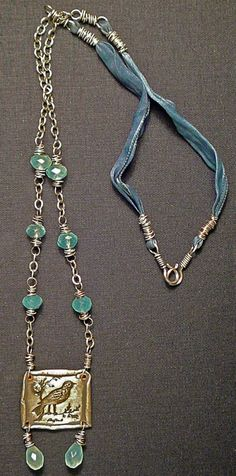 inspiration by n.b.--ADD BROWN SUEDE RIBBON TO ACORN PENDANT, AND ADD SOME SILVER CHAIN TO WIRE WRAP BEADS.