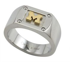 Polished Stainless Steel University of Michigan Flat Edged Ring With Gold Ionic Plated Block M Logo and Steel Rivet Accents. The Block M Logo Is Cut-Out to Reveal a 3D Design. This Ring Features a Comfort-Fit Setting. Great Gift for U of M Sports Fans and Alumni. www.belizadesign.com