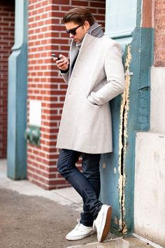 Something as simple as teaming a grey overcoat with navy skinny jeans can potentially set you apart from the crowd. White low top sneakers will add a new dimension to an otherwise classic look.  Shop this look for $227:  http://lookastic.com/men/looks/sunglasses-scarf-overcoat-skinny-jeans-low-top-sneakers/6887  — Black Sunglasses  — Grey Scarf  — Grey Overcoat  — Navy Skinny Jeans  — White Low Top Sneakers