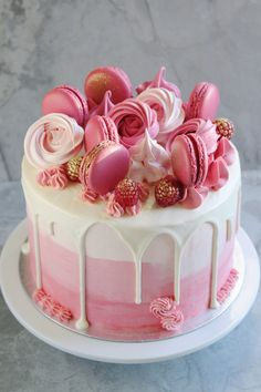 It's a girl! Pink baby shower cake with ombré buttercream, topped with macarons and meringue rosettes