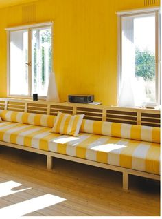 Summer feeling in this bright yellow corner! A large daybed with cushions and pillows in striped pattern.