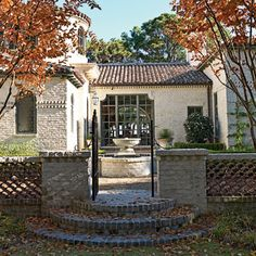 Mediterranean Flavor: Custom black ironwork and a low, lime-washed stone wall make a dramatic entrance to a formal garden at this Spanish-inspired home on the Georgia coast. Clipped boxwood hedges and Meyer lemon trees in aged Italian terra-cotta pots surround a limestone fountain for an added statement.