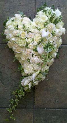 A swinging heart, based in 6 different type of ivory and white roses, with a Calla Lily  and Ivy Trail crown with an Ivy edge.