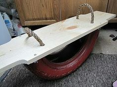 Teeter totter made out of half an old tire, wood, and rope.