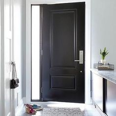 A black front door opens to a black and gray foyer filled with a black sliding door cabinet topped with marble facing a closet door illuminated by a nickel and glass flushmount light. House Front Door, Glass Front Door, Black Doors, White Doors, Dark Grey Front Door, Silver Door Handles, West Facing House, Front Door Hardware, Foyer Design