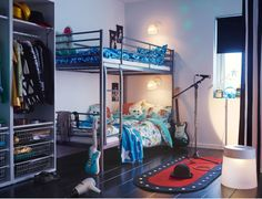 A children's room with a silver-coloured bunk bed made with bed linen in turquoise and blue. On the floor there is a rug with LED lighting that looks like a stage.