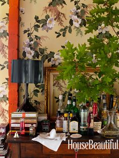 vintage wallpaper, a childhood desk-turned bar, black lamp, live plant, it's all just so darn perfect.