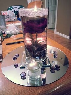 Purple wedding centerpiece. Double mirrors on the bottom, with three tealights/candle holders surrounding cylinder vase, with some bling & sparkle!! Trial 1!! Beauty & the Beast inspired!!!!!