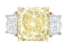 Platinum, High Karat Gold, Fancy Yellow Diamond and Diamond Ring.  22 kt., centering one cut-cornered rectangular modified brilliant-cut Fancy Yellow diamond approximately 10.23 cts., flanked by 2 trapezoidal-shaped modified brilliant-cut diamonds approximately 2.22 cts. Size 6 1/4, with bumpers. Via Doyle New York.