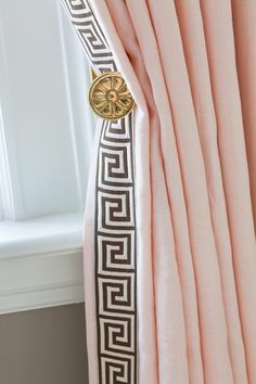 pink linen drapes with greek key trim and brass tie backs designed by anne hepfer