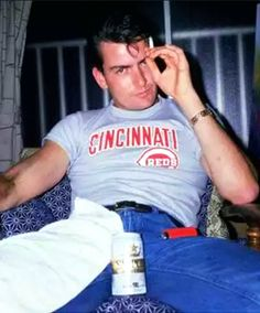 American actor Charlie Sheen smokes a cigarette while sitting with a. Two And Half Men, Half Man, Charlie Sheen Young, Charlie Sheen Shirts, Tom Hanks, Cincinnati Reds, Queen, Celebs, Men's Clothing