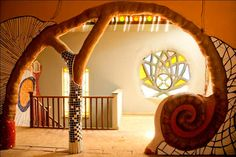 Cob house.Glasses in different shades to bring out the light from out in a more reflective manner and to lit the inner space would be ideal for a spiritual place to reflect upon ourselves.