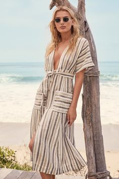 The Free People Monday Light Grey Striped Midi Dress is the best possible way to cheer up a dreary day! Cotton-linen blend woven fabric, with a stripe print shapes wide, cuffed short sleeves and a sultry plunging bodice. Midi skirt with tying waist sash, a button-front, and patch pockets.