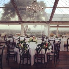 Romantic marquee wedding styled by Green and Bloom. Flower and foliage detailing to back of bride and grooms chair, giant garden styled arrangements in glass footed vessels, maypole fairy lights, chandelier, clear marquee, wedding Brisbane.