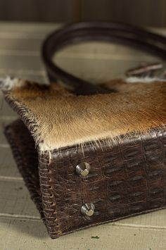 South African antelope gives you a thick hair-on front, finished with croco embossed Italian cowhide leather surrounds the rest. Made in the USA.