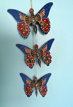 This lovely set of three butterfly wood carvings features rich contrasting colored paint on hand carved wood.