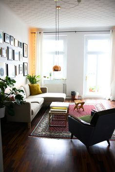 An Artful Retreat in Berlin, Germany  A lot has changed in the living room over the past four years — curtains, chairs, light fixtures, tables. But the constants have always been the cozy IKEA couch, vintage Indian rug, and natural light | Design*Sponge