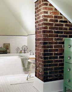 bath in the attic. exposed brick chimney column.