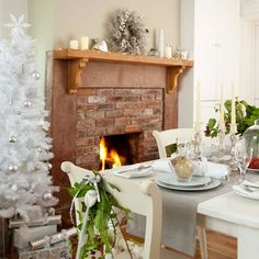 White Christmas dining room with cosy fireplace and faux tree