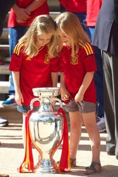 Princess Leonor of Spain (L) and Princess Sofia of Spain peer into the UEFA EURO 2012 trophy as King Juan Carlos I of Spain receives players of Spain's victorious national football team at Zarzuela Palace on July 2, 2012 in Madrid, Spain.