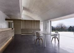 Concrete structure of this Zurich home plays off against the soft palette of natural oak and travertine stone, which is interrupted only by MDF Italia's Flow Chair and Tense Table.