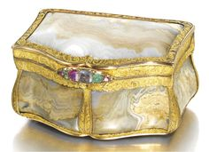 A GOLD AND HARDSTONE SNUFF BOX, KEIBEL, ST PETERSBURG, 1835 of cartouche form, the panels carved of striated brown and milky agate, set in gold cagework mounts chased with scrolls, flowers and shells on sablé grounds, the bombé sides and corners with acanthus, the raised thumbpiece set with diamonds, rubies, emeralds and a sapphire, 72 standard, in original gilt-tooled red leather case | JV