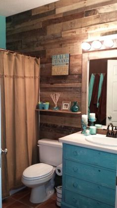 Our hall bathroom re-done. Reclaimed wood walls. Thrift store dresser, that was repainted, destressed and sanded. Thrift store solid surface counter top and bowl. Other walls are brown and turquoise. Absolutely love it. Final touch is Mason jar lights.