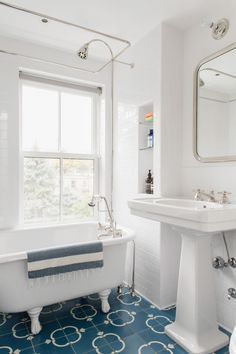 Claw-foot bathtub and pedestal sink from Waterworks and floor tiles from Town & Country Surfaces; mirror Restoration hardware