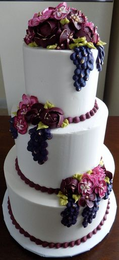 Wine themed buttercream wedding cake.Three tier buttercream wedding cake, decorated with an assortment of wine colored and burgundy buttercream flowers as well as grape clusters with gold hi-lights