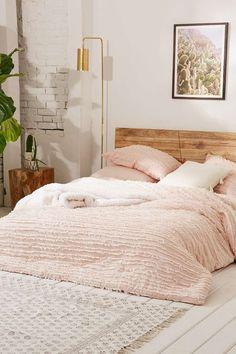 Housse de couette à franges effilochées Urban Outfitters chambre pastel rose poudree lampadaire laiton parquet blanc blanchi tete de lit en bois brut