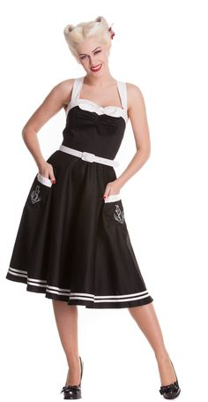 A nautical dress with a retro style perfect for balmy summers. This dress is black with white trim on the skirt, pockets bustline and straps. The bust has a white bow in the centre with a gathered effect underneath. The shoulder straps are adjustable at the back and can be worn crossed or straight. The bodice has smocked panels to either side to give a perfect figure hugging fit.