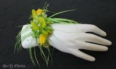 Prom Flowers - Wrist corsage of green feathers, green button mums, yellow freesia and green pearls.