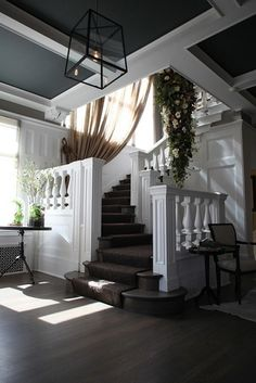 Beautiful entry / foyer. Changes: plantation shutters instead of the curtain on landing. And, what is with the handing plant? Not all with panels w/ ballisters, railing...change --add a touch of dark wood/black paint.