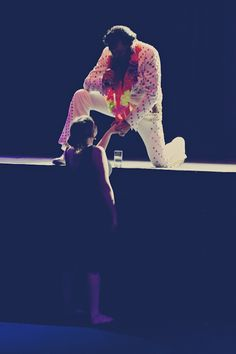During a concert a girl walks up to the stage and looks at Elvis. He comes and kneels down to shake her hand. This is a priceless picture of love shown to someone else.
