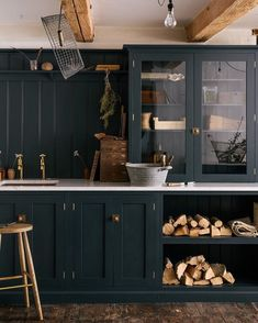 Navy blue cabinets with glass and open shelving and wood beams