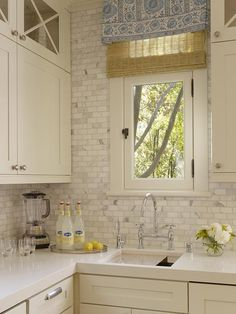 head-over-heels in love with this kitchen:  love the natural shade w/blue + white roman shade or valance; x-glass cabinets; gorgeous marble tile from counter to ceiling; gooseneck faucet; window; cabinets + pulls -- just perfect
