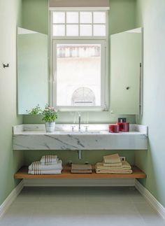 Bancada do banheiro. Espelhos laterais se revelam armários versáteis e leves acima da bancada de mármore carrarinha (Foto: Sambacine)