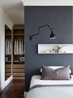 Une suite parentale avec dressing en bois, peinture sombre et niche astucieuse.
