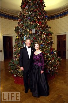 President George W. Bush and Laura Bush stand before the Blue Room Christmas Tree Sunday, December 8, 2002 prior to hosting a reception for the Kennedy Center Honorees. Mrs. Bush is wearing a floor length gown designed by Arnold Scaasi. White House photo by Eric Draper.