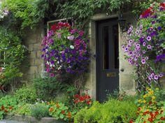 creamy stone, darker mortar, dark and white window frames, dark door, curb edging on flower beds, colorful climbing flowers