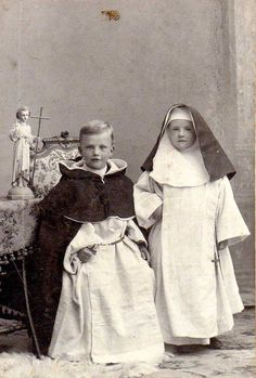 """For Roman-Catholic little boys, until about the 1960s it was very popular to play """"mass"""", inclusive all the cheaply produced altar utensils and a tiny book of prayers/missal. To be serious they also dressed up like little priests. However, pictures of boys and girls, dressed up as monks or nuns are rather scarce in the Netherlands. Albumen print c. 1920. The little statue is an engelic guardian, who would guide and keep the little souls until they were confirmed within the RC community."""