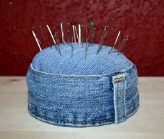 denim pincushion...she cut the waist band off, sewed it into a ring, then stuffed a tin - a tuna can would work - stuffed it, added piece over the top and glued the ring to the can and to the top piece. Nice and sturdy pincushion!