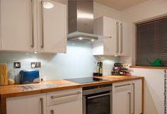 Blue glass kitchen splash back with white gloss units