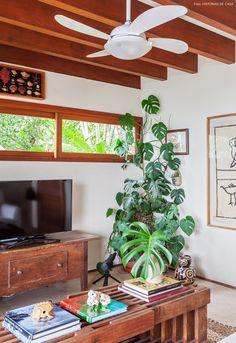 Vigas de madeira e janelas com vista para o verde nessa casa de praia em Ilhabela.