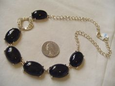 Lovely vintage necklace, solid black prong set stones with inlaid rhinestones on one accent link on silvertone chain.