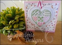 This gorgeous cross stitched christmas card is made up of lots of little designs within the love heart shape. Complimented with ribbon and wording. Available over at Tulipacious Designs.